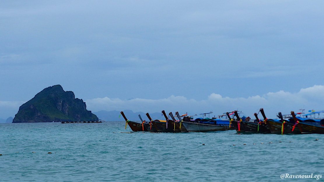 Limestone cliffs and long tailed boats at Phi Phi Islands